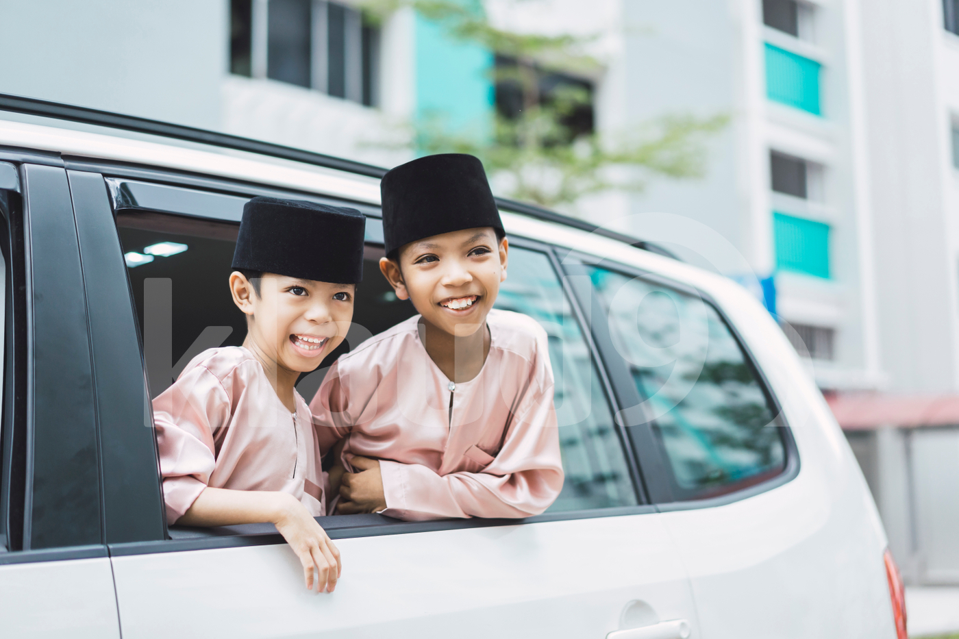Two Malay boys looking out of the car window
