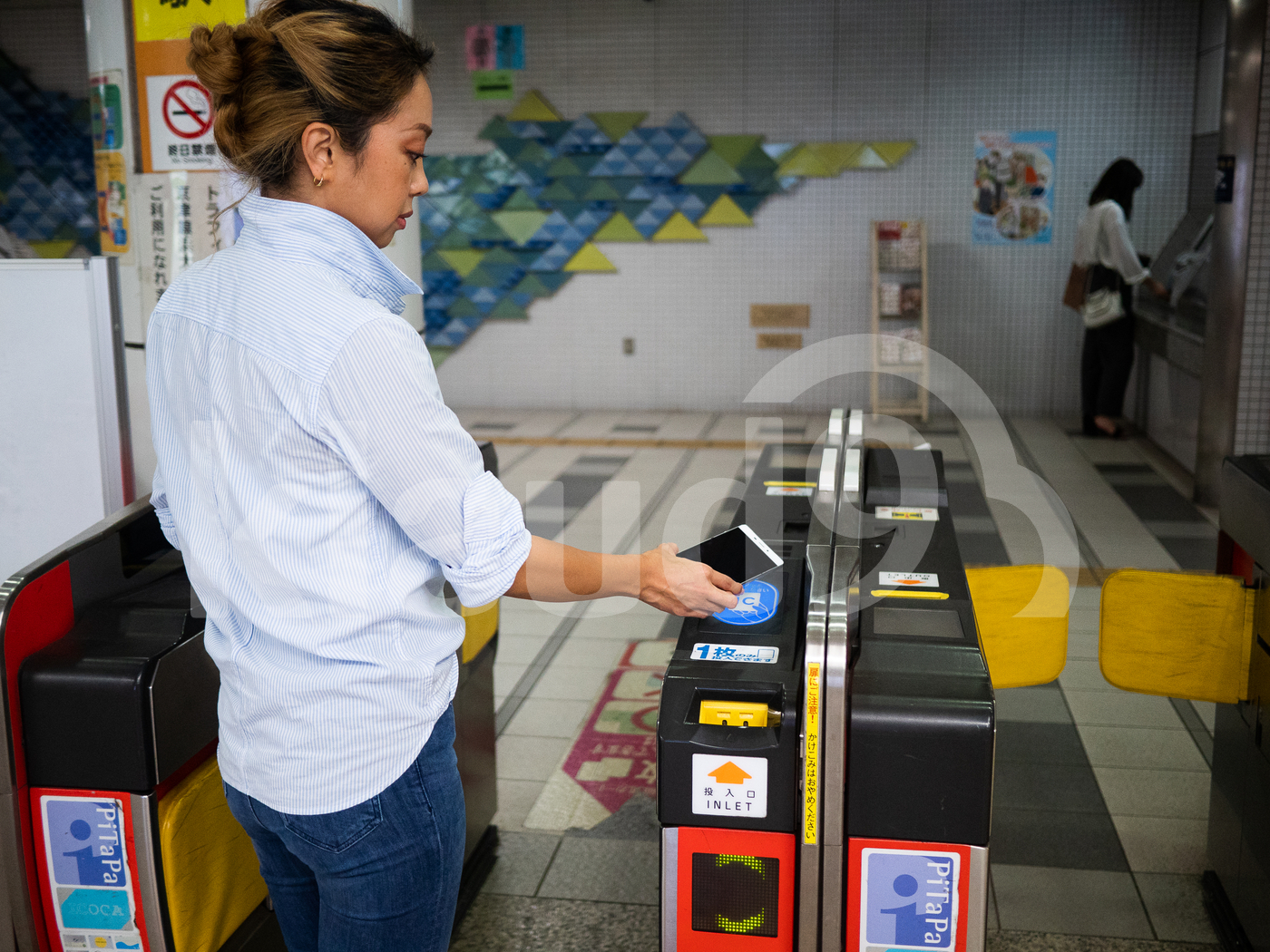 Japanese woman making payment with mobile in public transport
