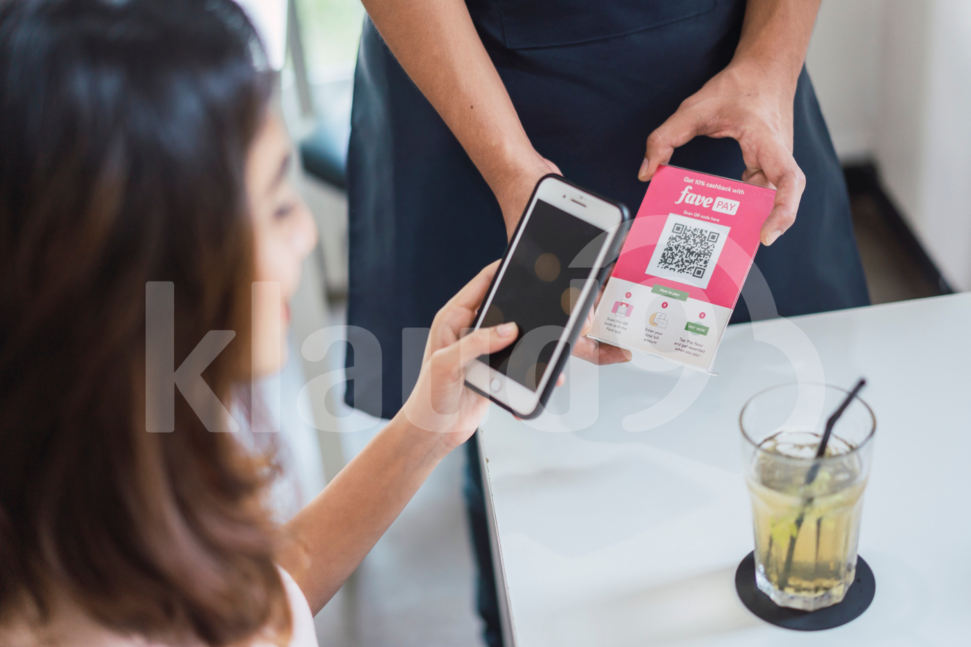 Woman scanning QR code to make payment
