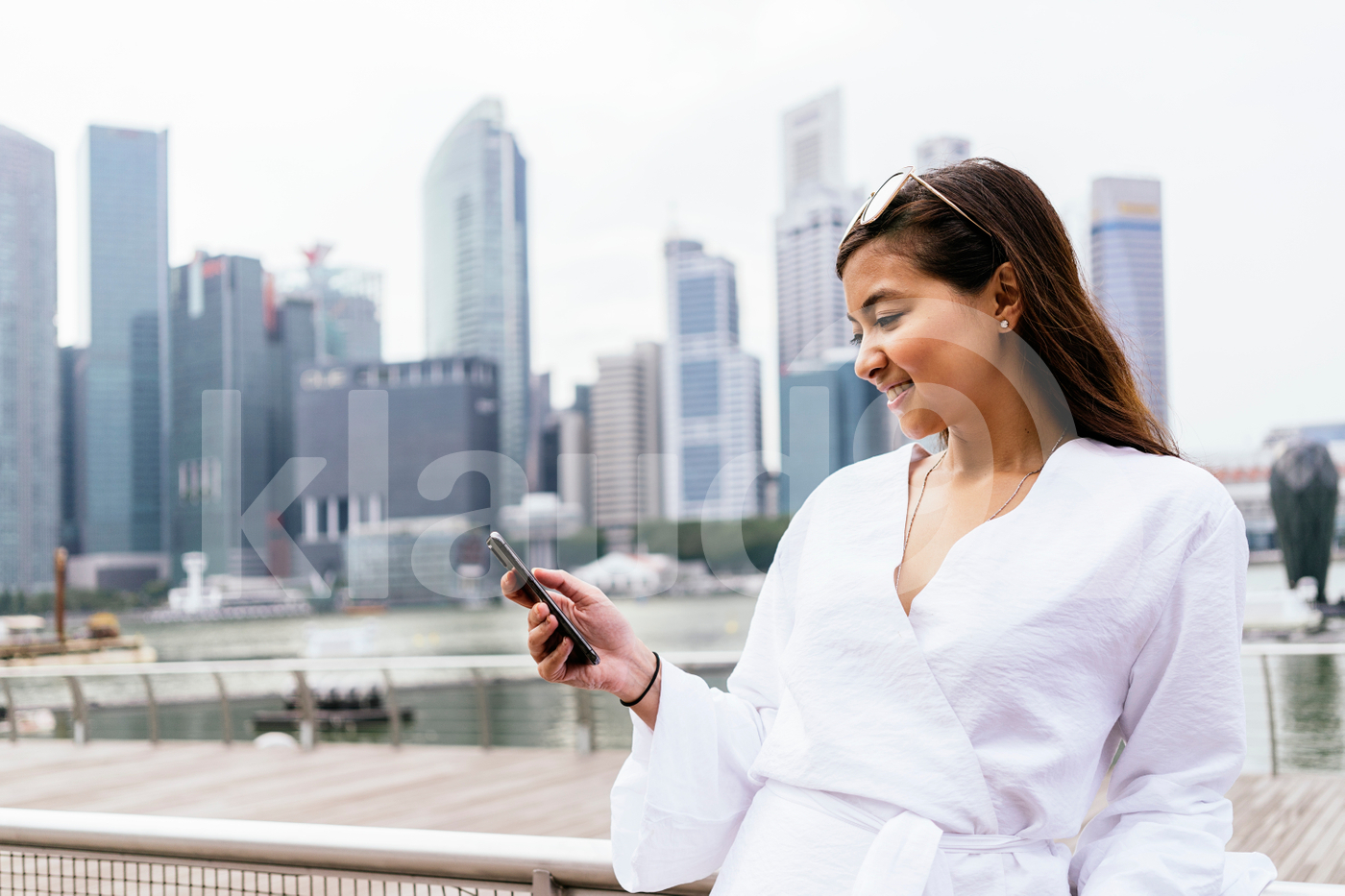 Asian woman standing  outdoors using smartphone
