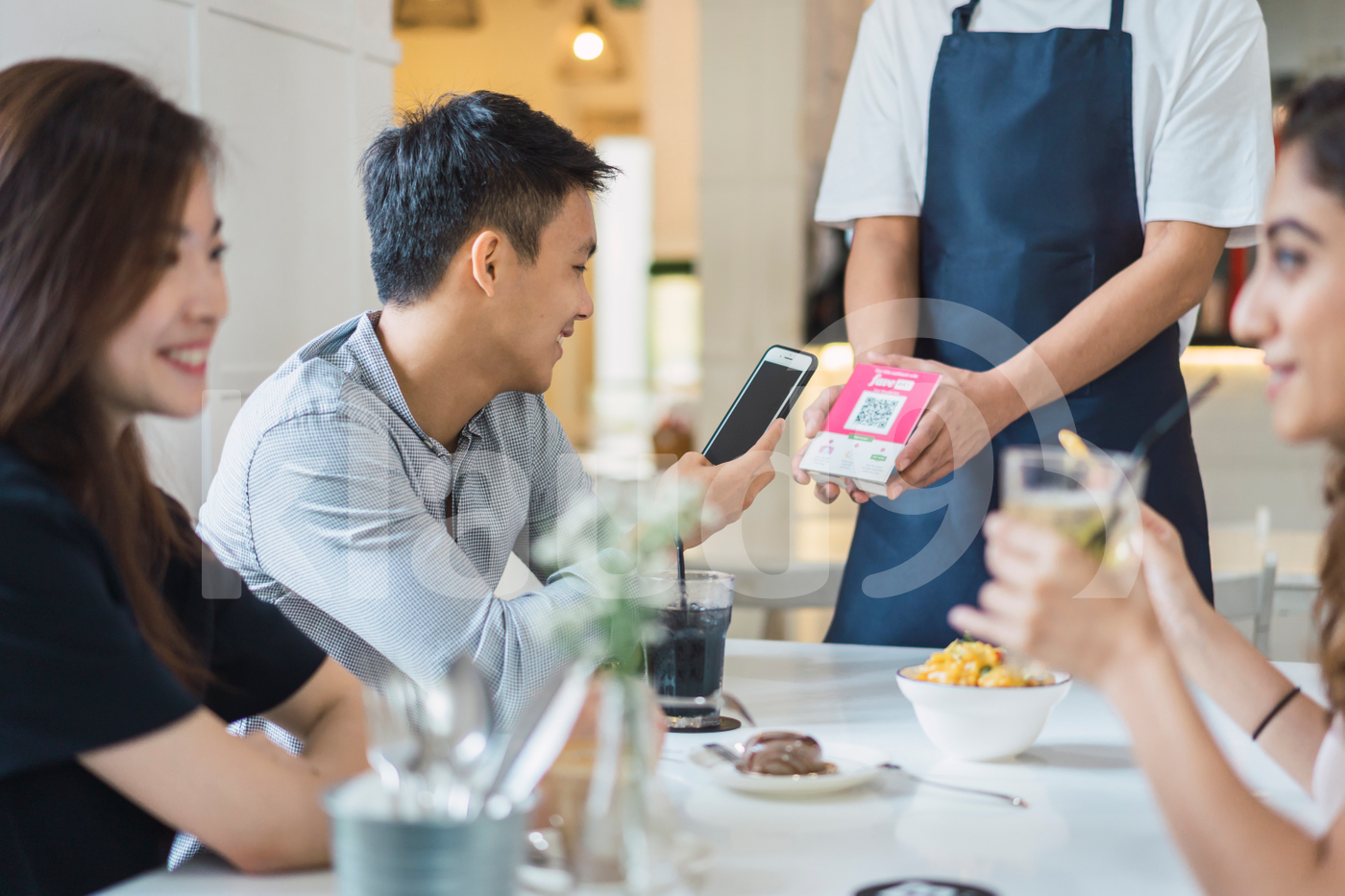 Asian man making payment with mobile at table
