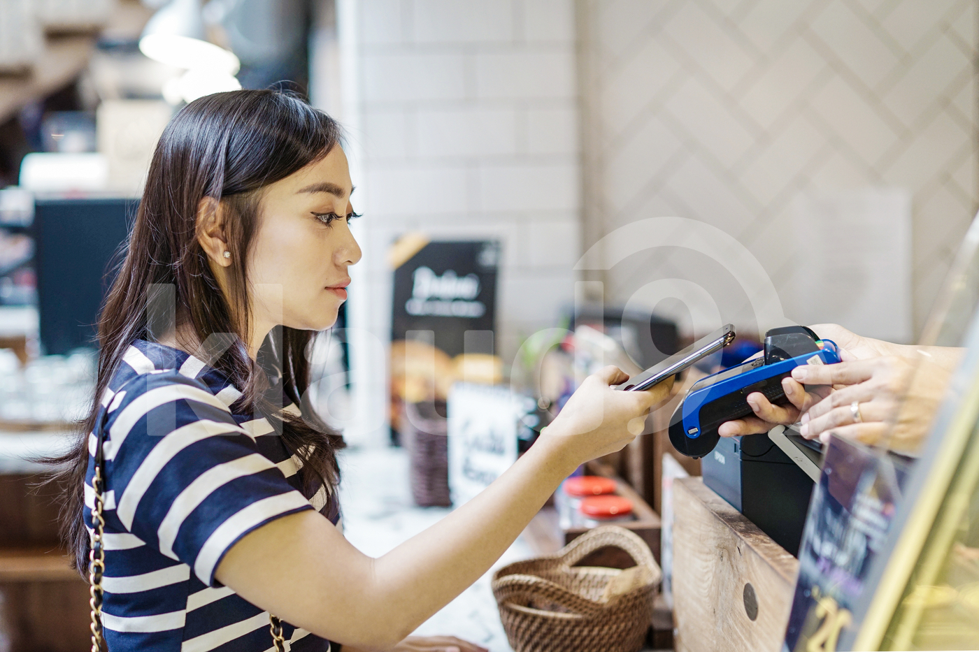 Asian woman with smartphone using contactless payment at restaurant