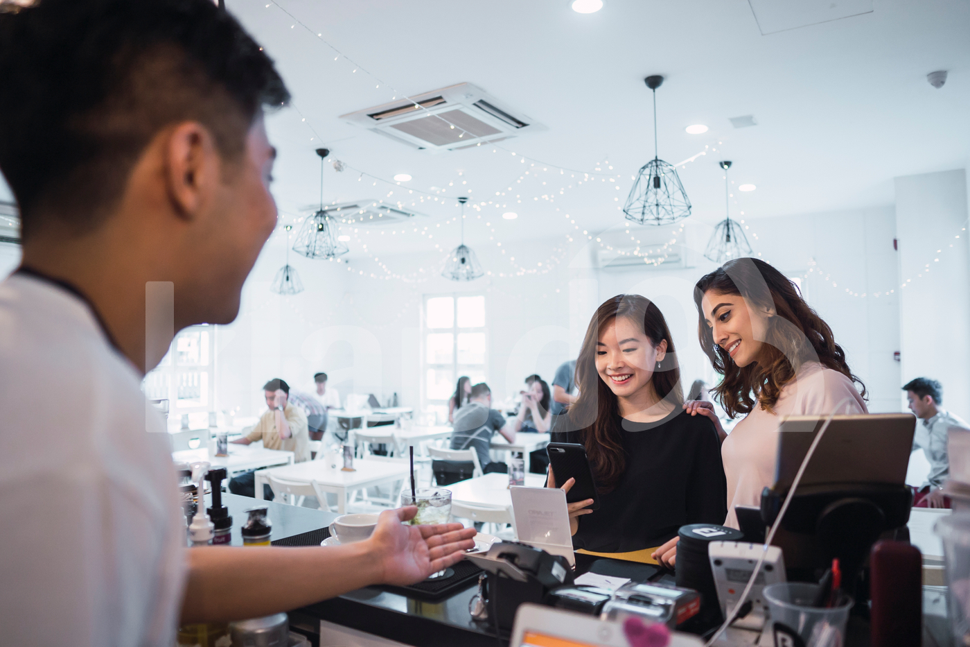 Asian friends making mobile payment in a coffee shop