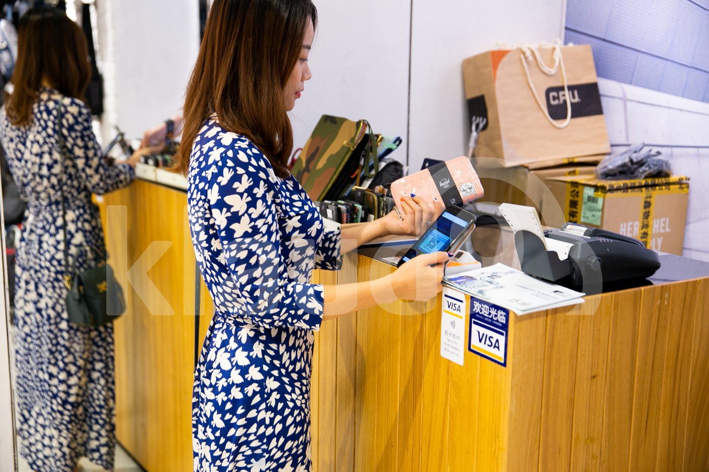 Young adult woman scanning QR code to pay at a shop