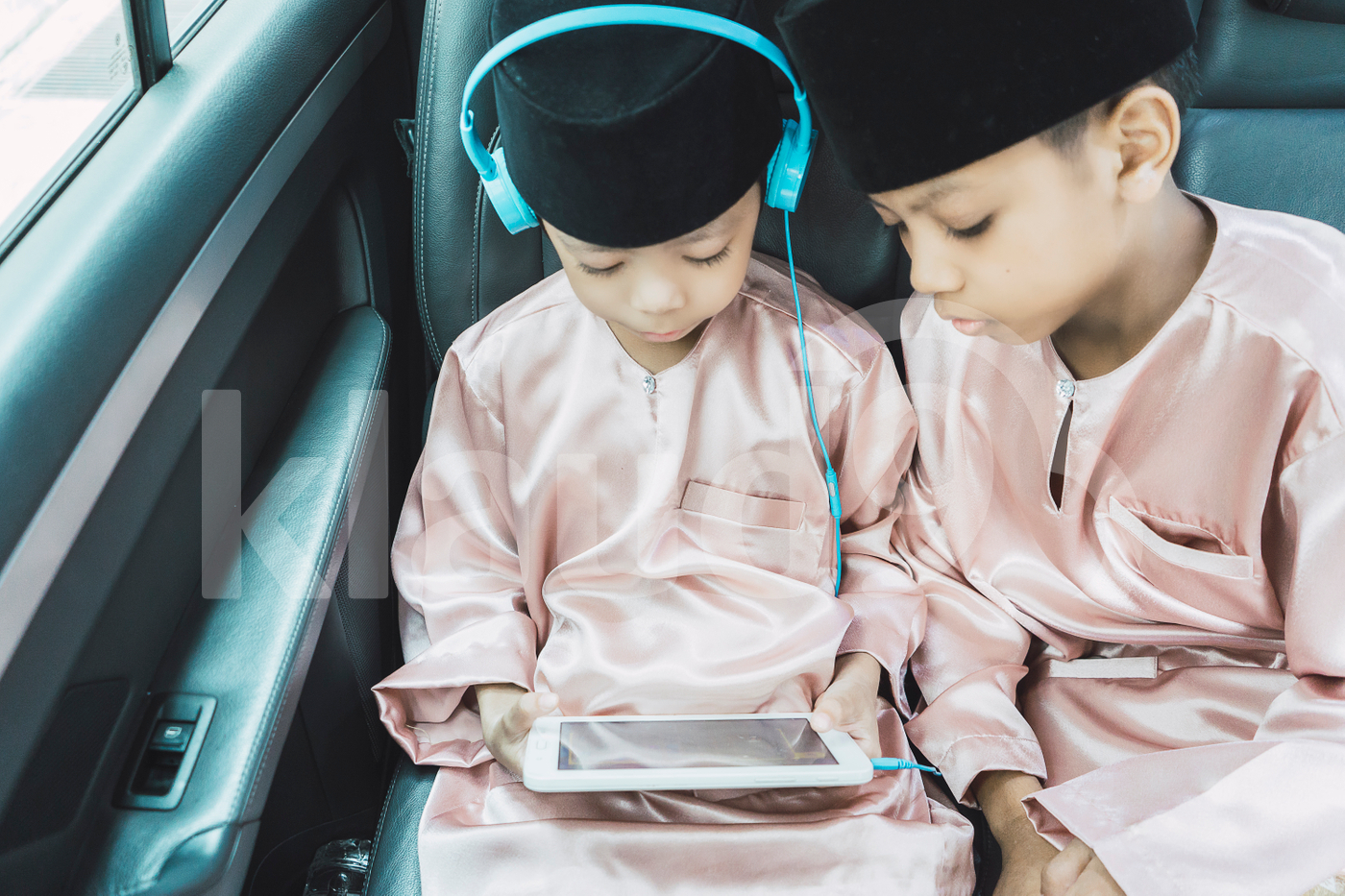 Siblings watching tablet in the car