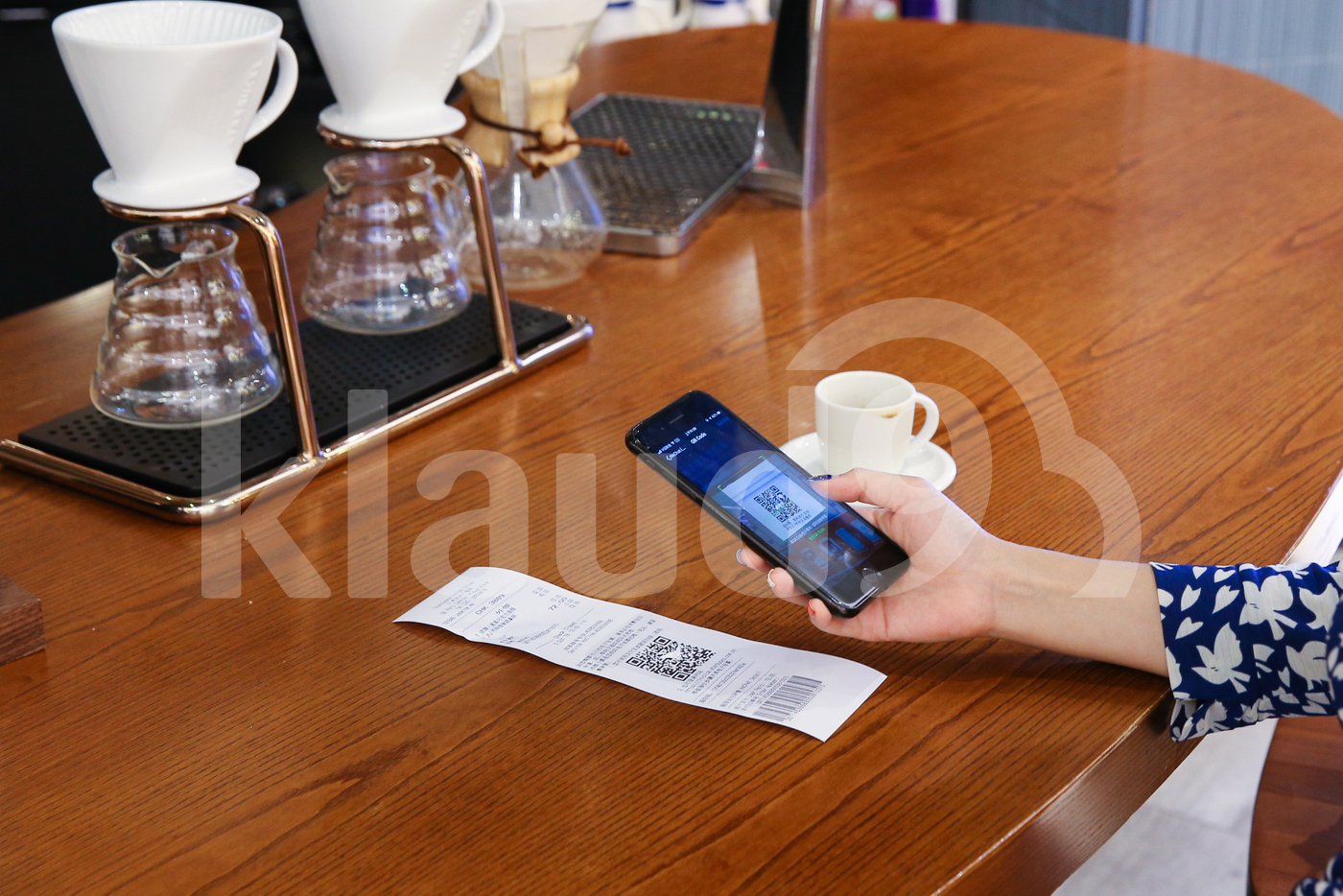 Woman making payment with mobile by scanning QR code