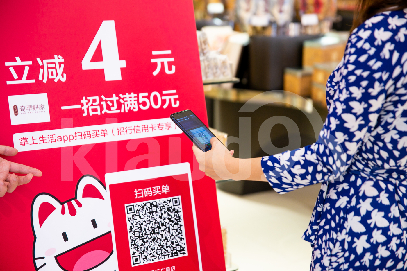 Woman making payment with mobile by scanning QR code in a  shop