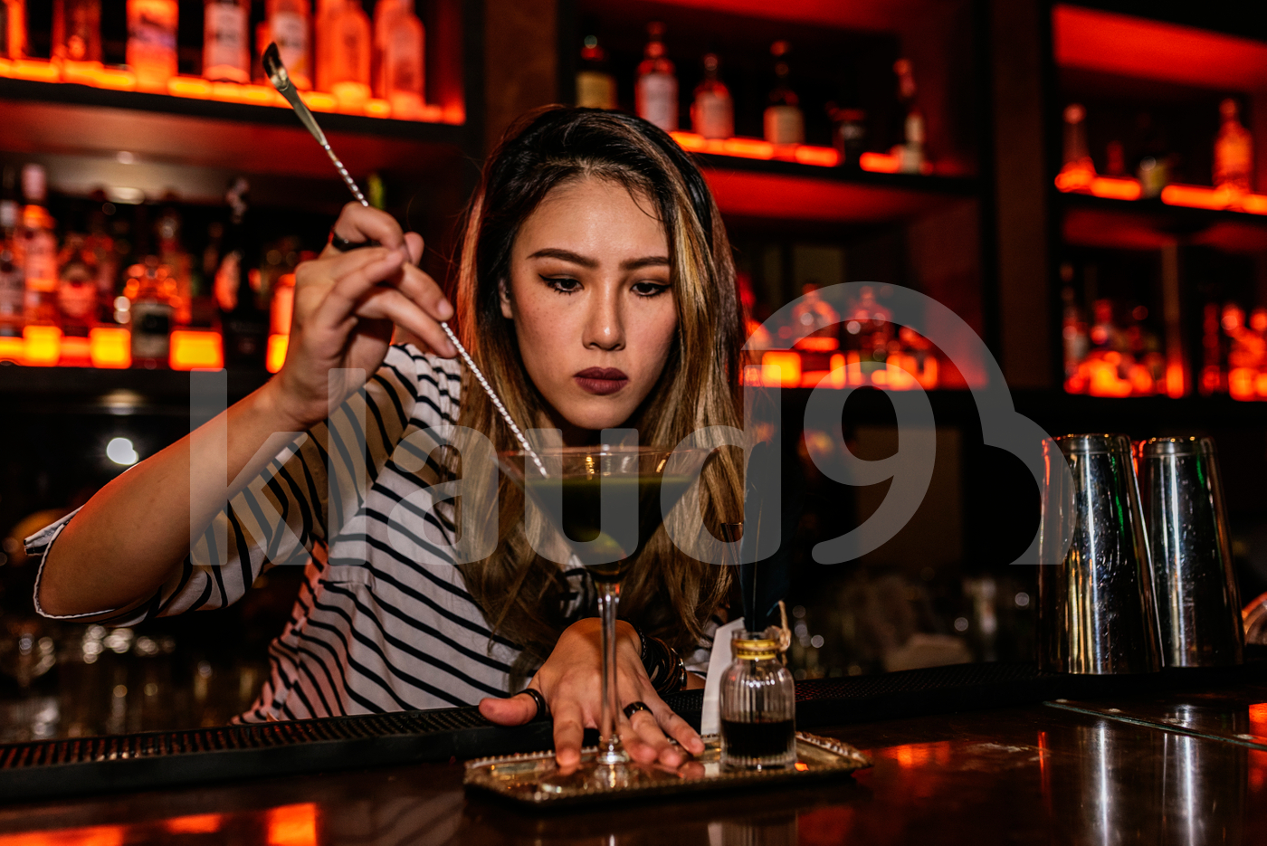 Asian bartender stirring cocktail drink using bar spoon