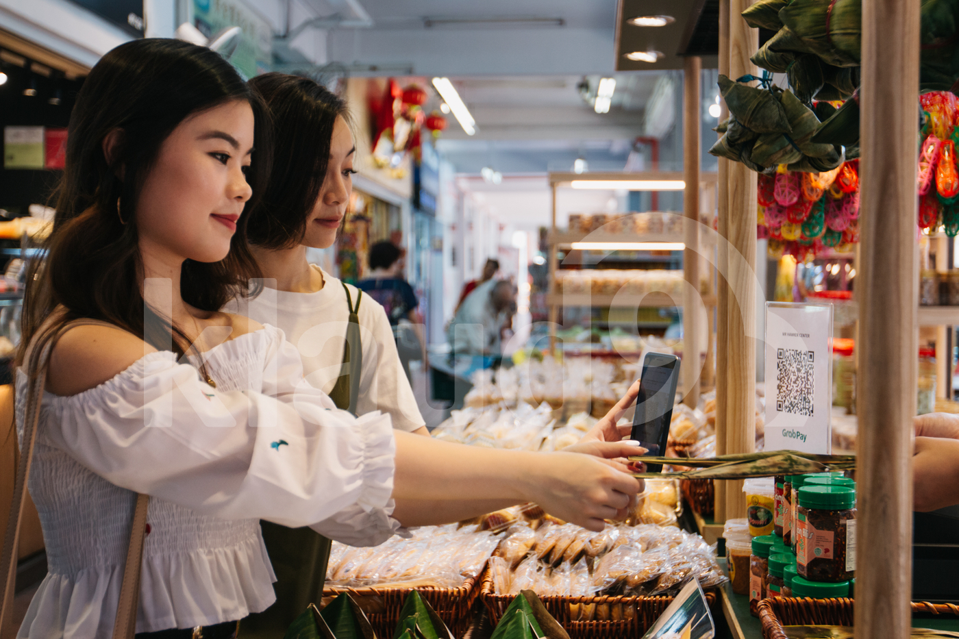 Asian friends making payment with mobile in a local shop