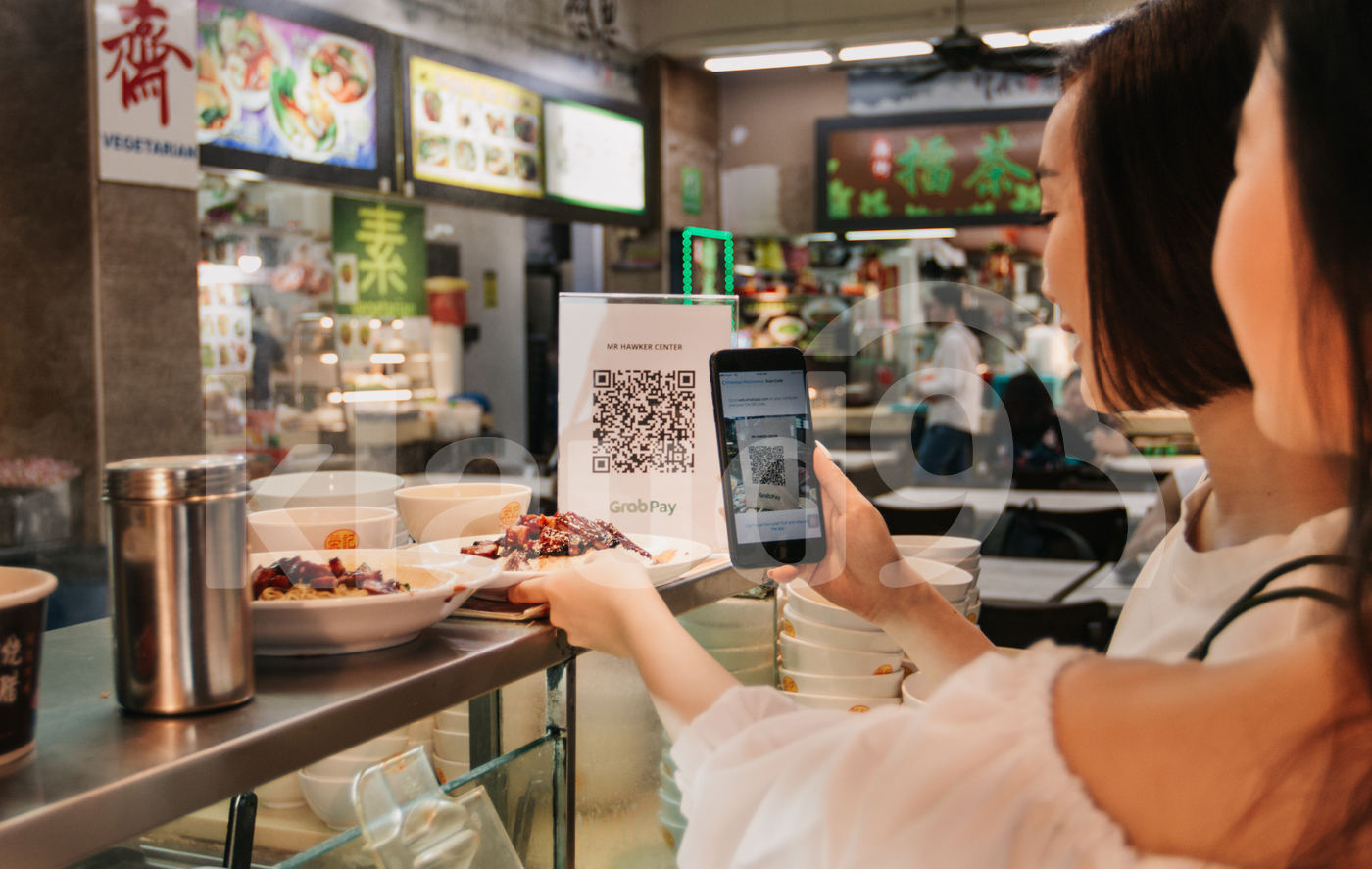 Young Asian friends scanning QR code to make payment in local food court