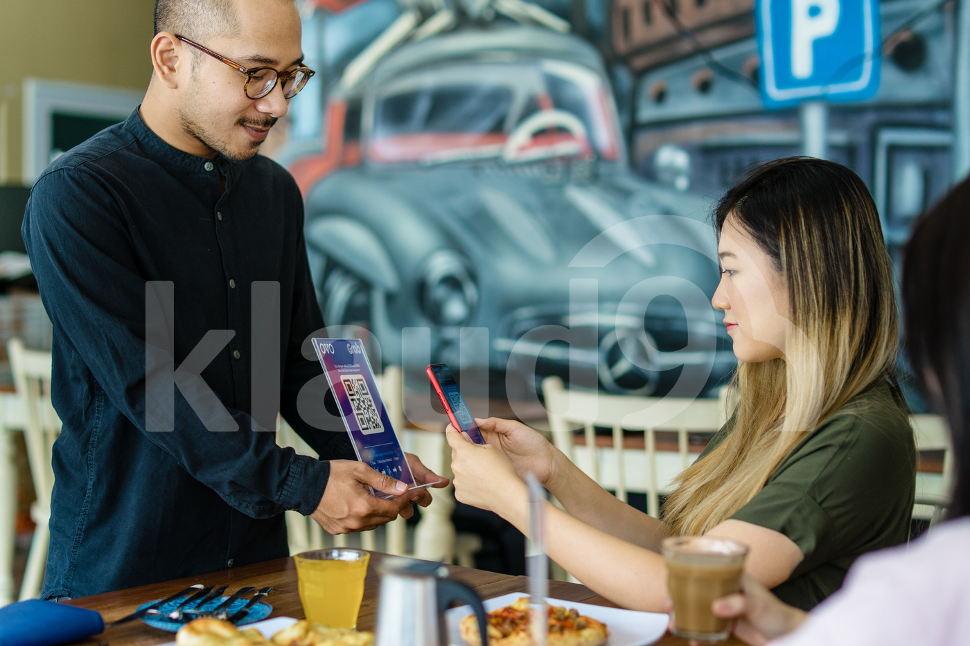 Young adult woman scanning QR code in a restaurant