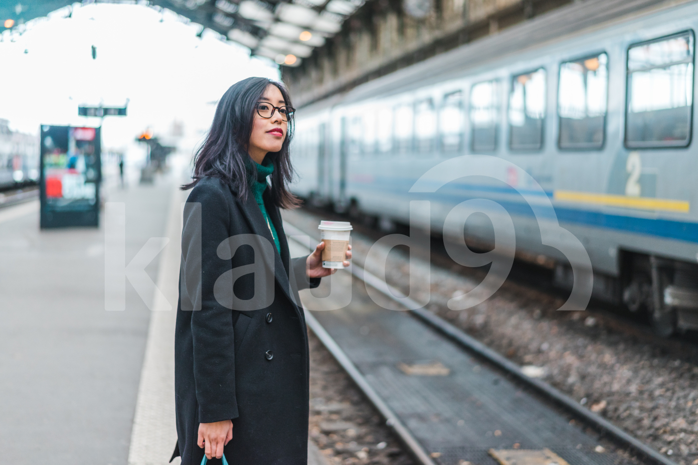 Asian woman waiting for a train holding a coffee cup