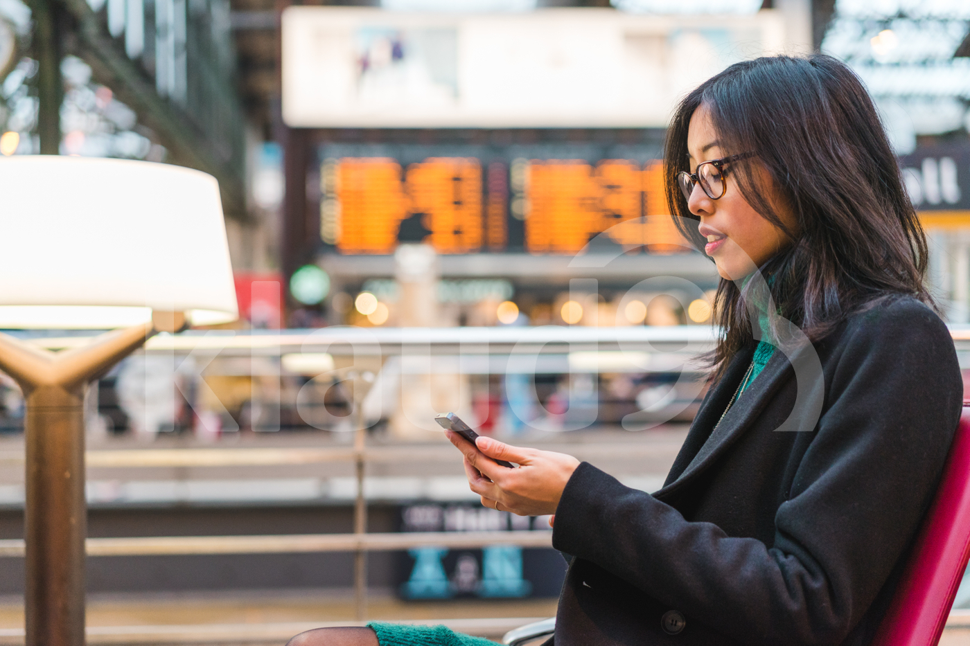 Young adult Asian woman looking at her mobile in a train station