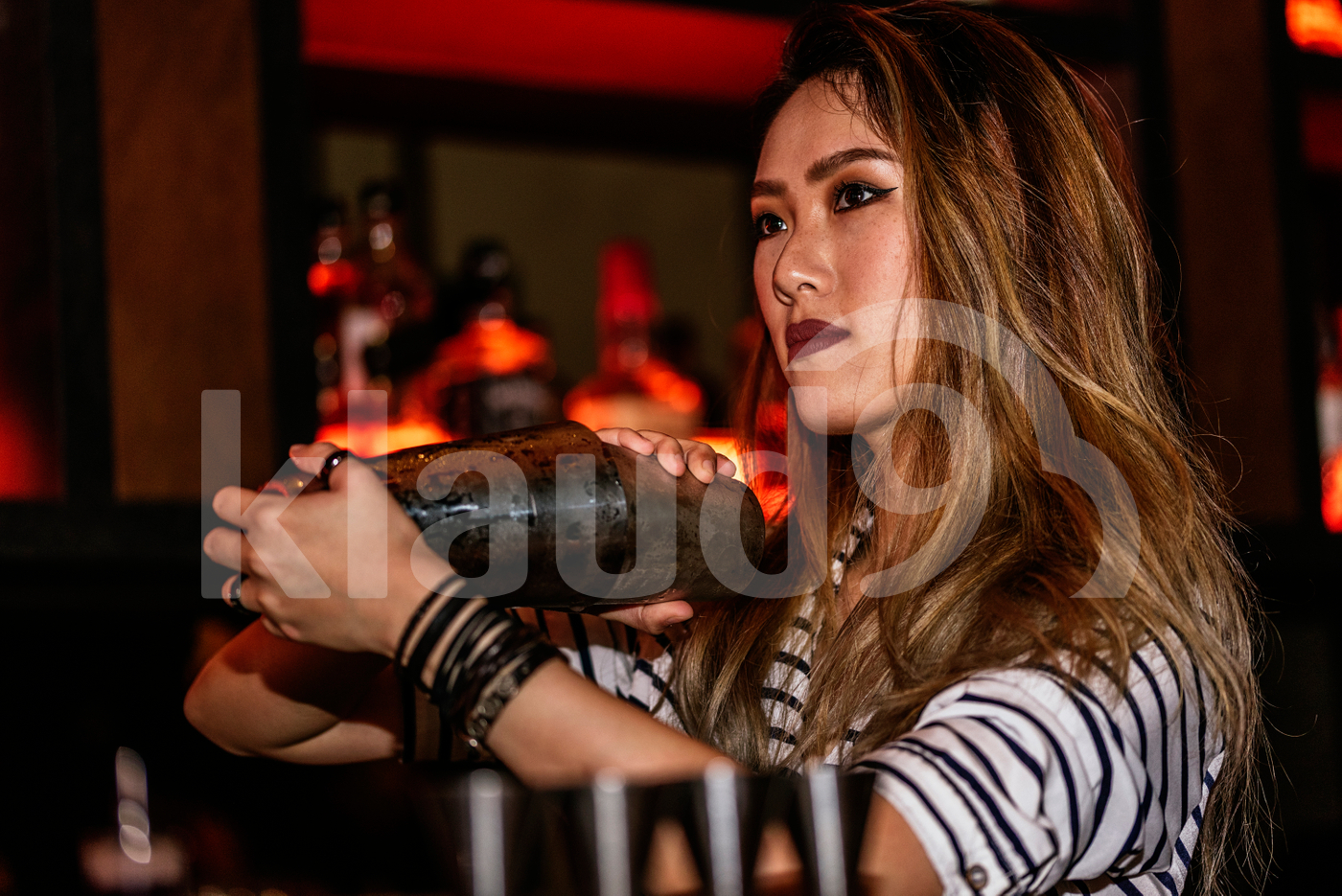 Female Asian bartender mixing drink using shaker