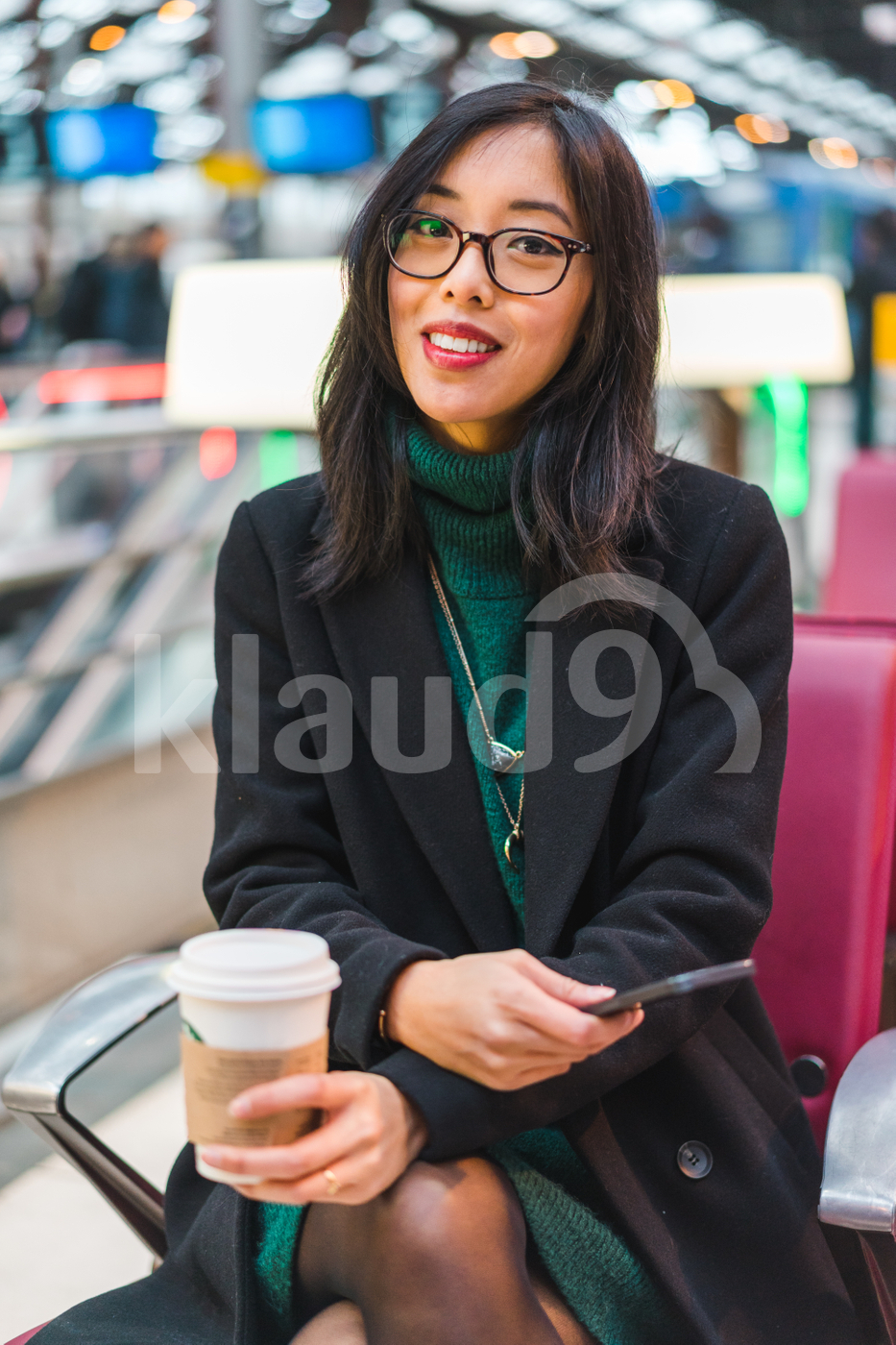 Young woman sitting in a train station holding a coffee cup