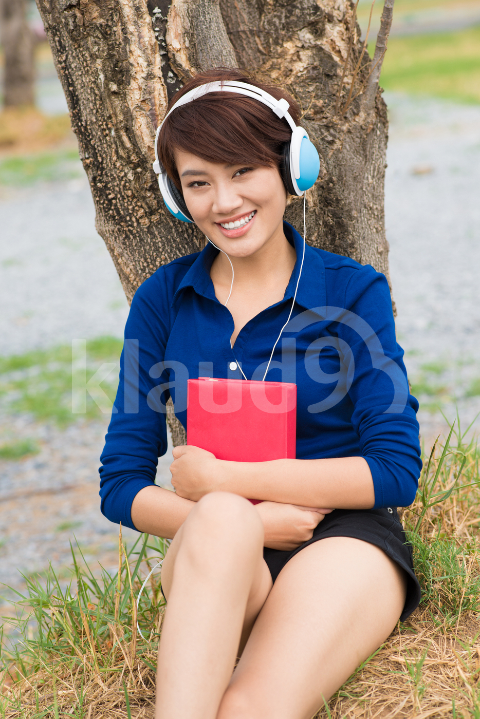 Portrait of a young girl in headphones sitting and looking at camera