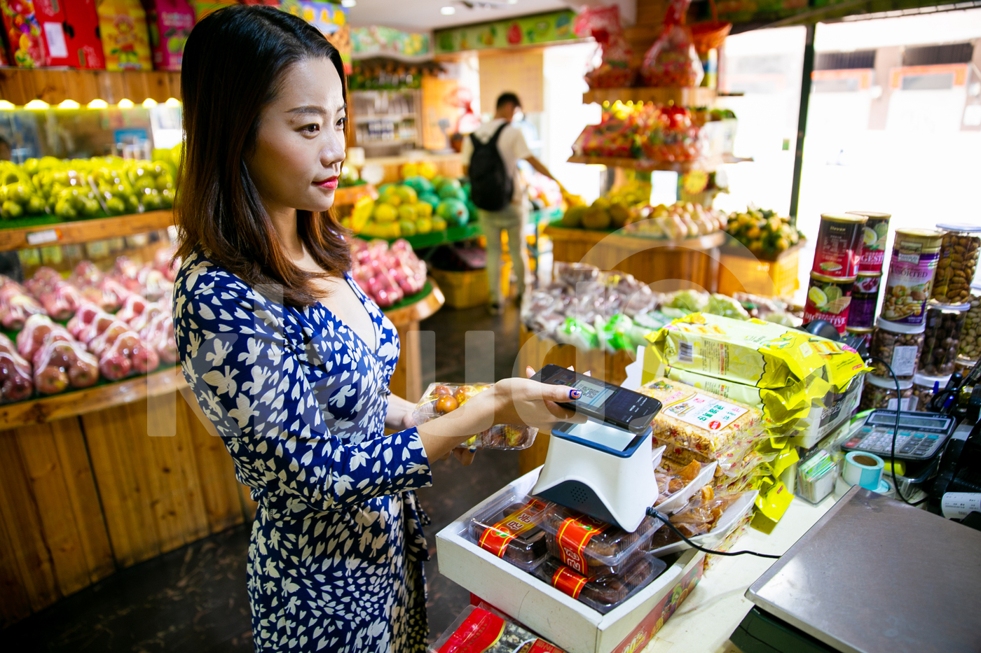Asian woman making payment with mobile in a local shop