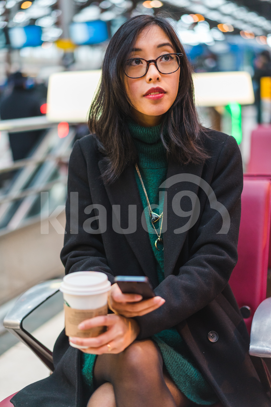 Young Asian woman sitting in a train station holding a coffee cup