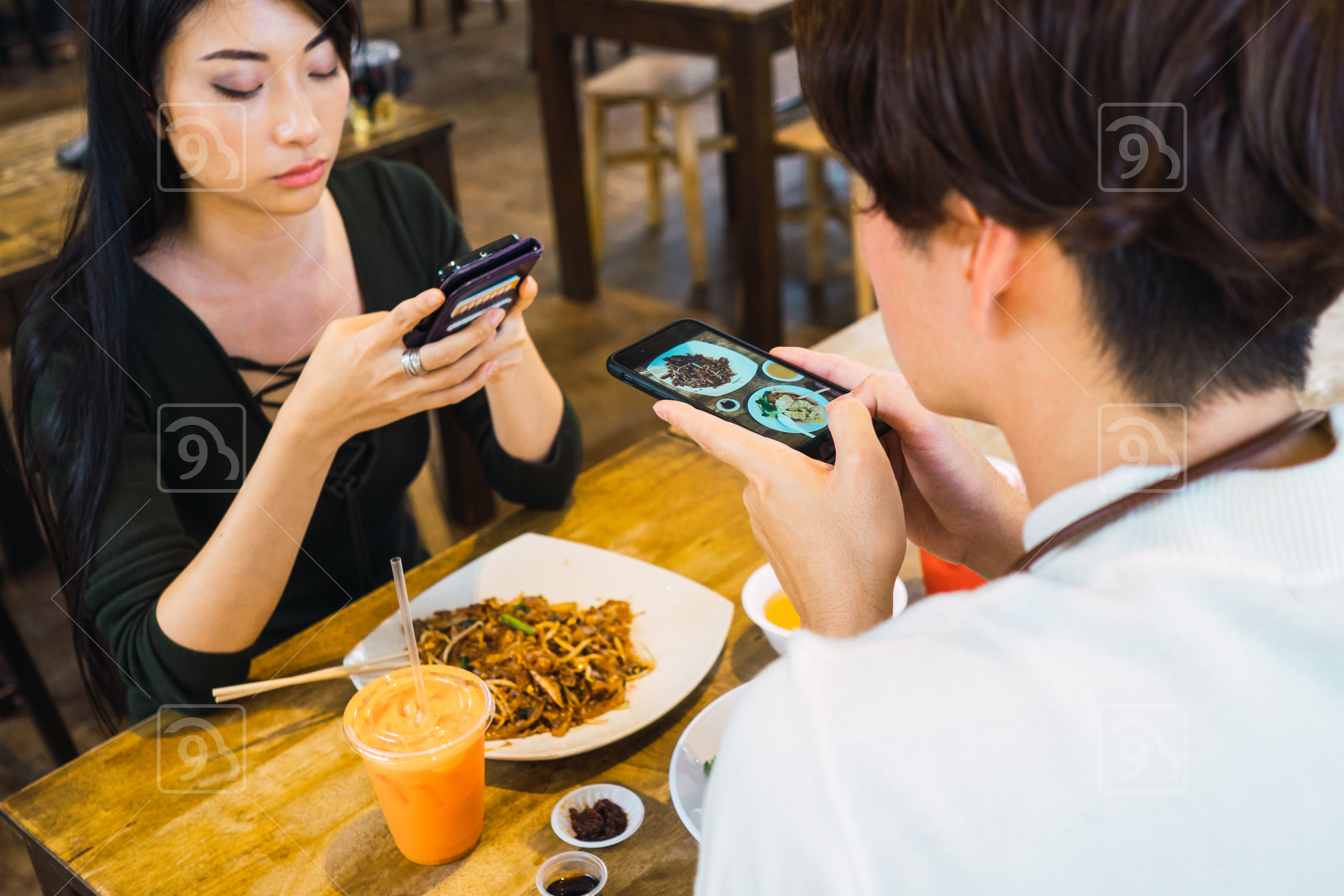 Asian man and woman taking food selfies
