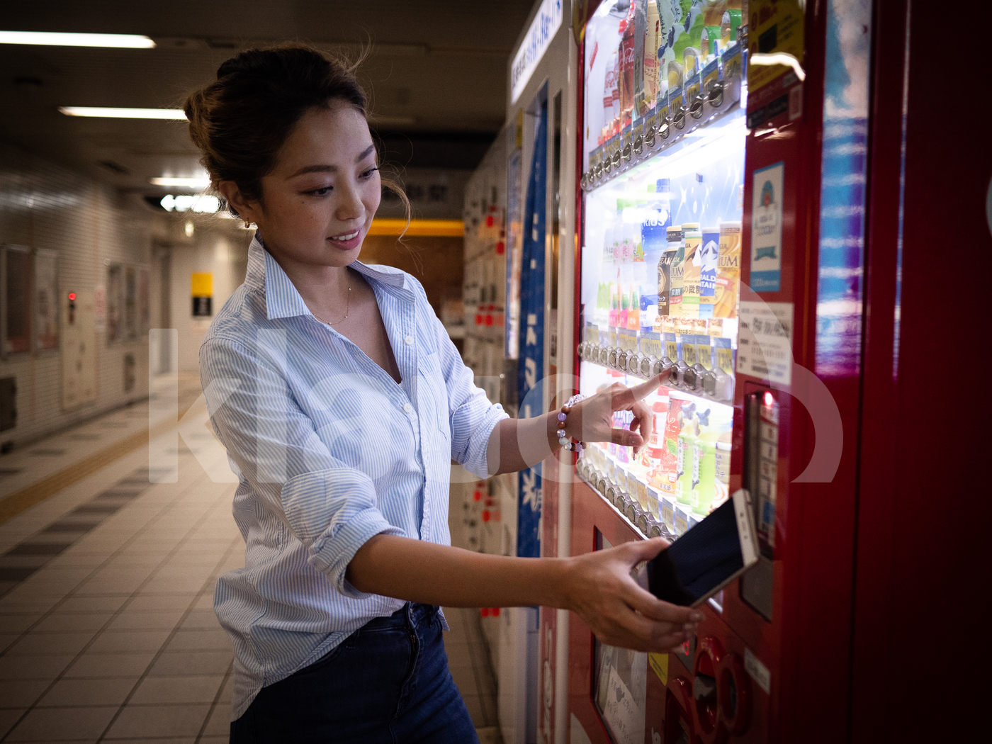 Young Japanese woman paying with mobile at vending machine