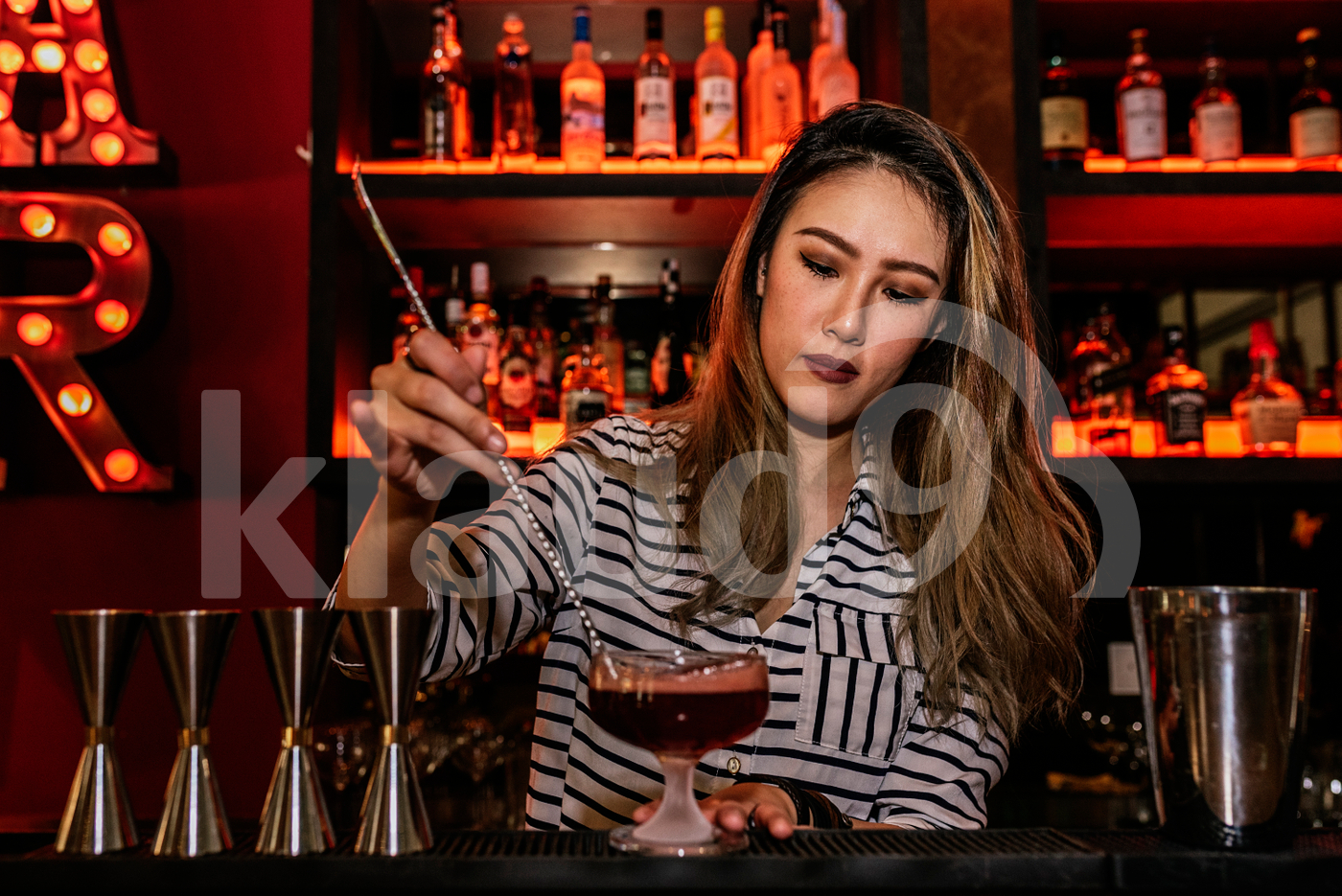 Asian bartender stirring drink using bar spoon