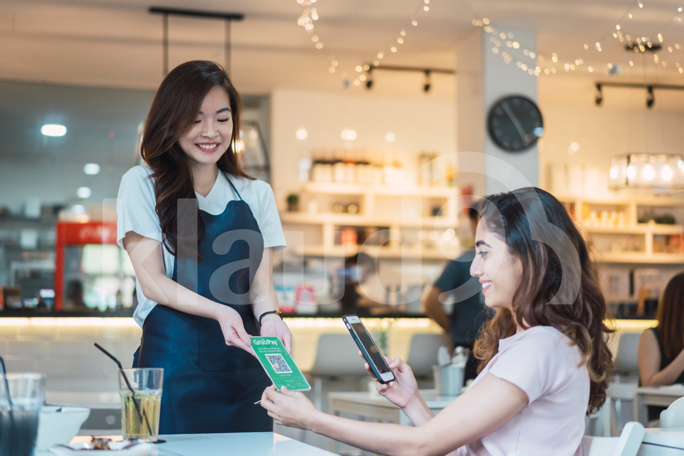 Young Asian woman scanning QR code at table to make payment