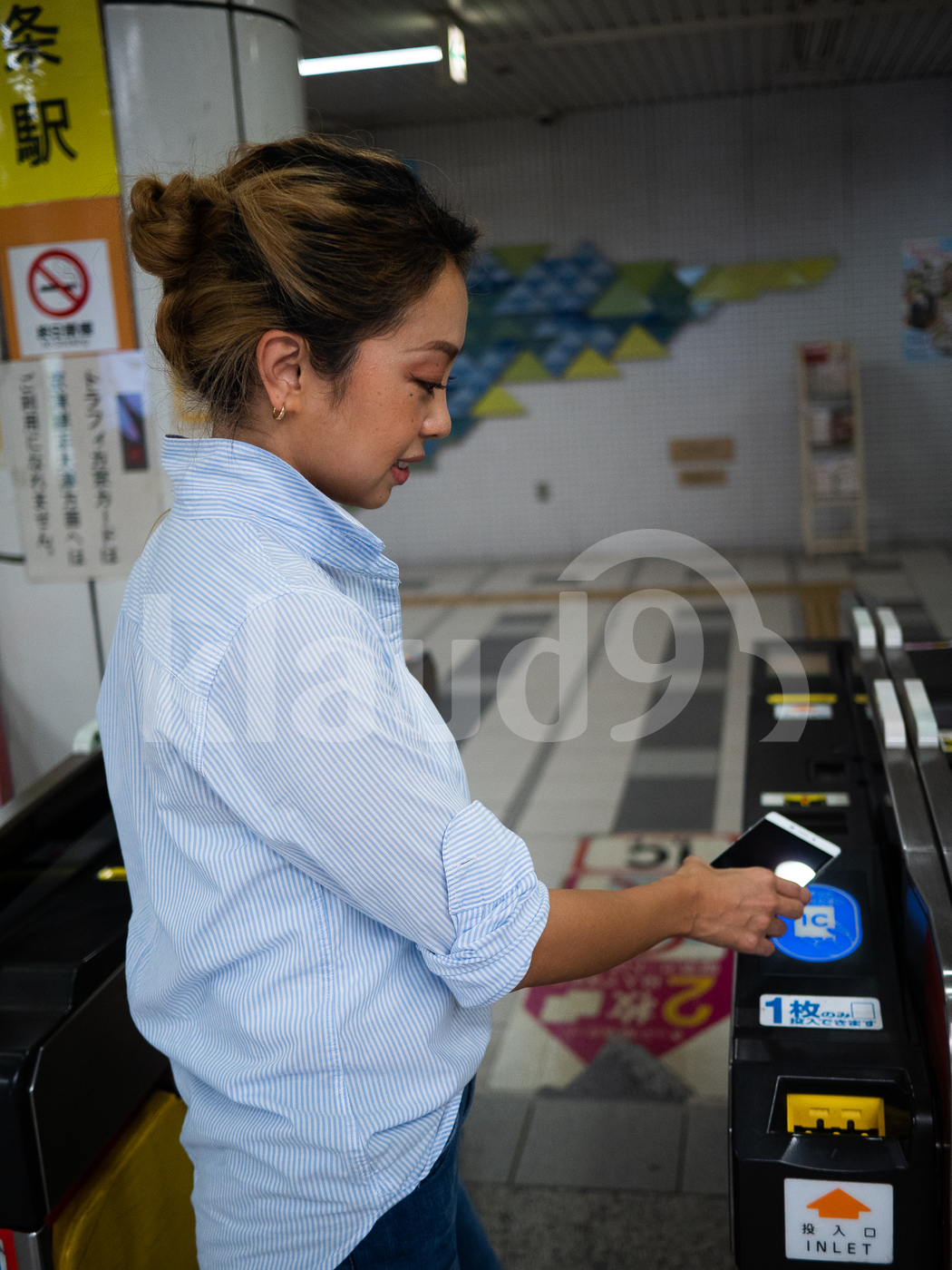 Japanese woman making payment with mobile in train station