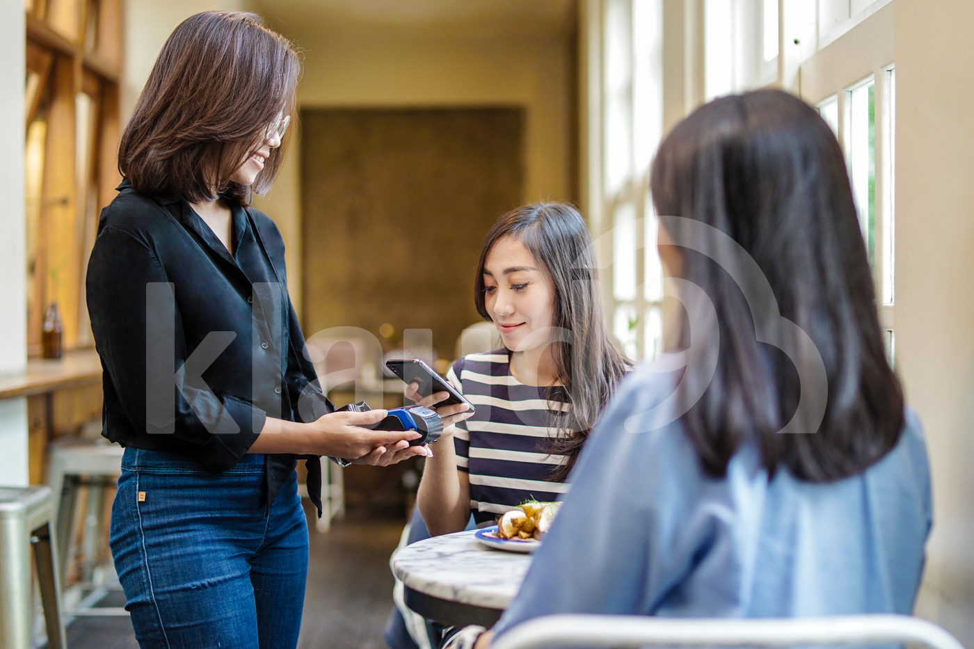 Young Asian woman making payment with mobile in a coffee shop
