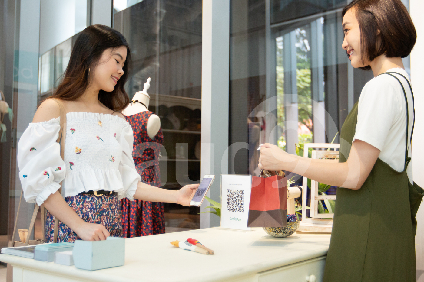 Young Singaporean woman making payment with mobile in a shop