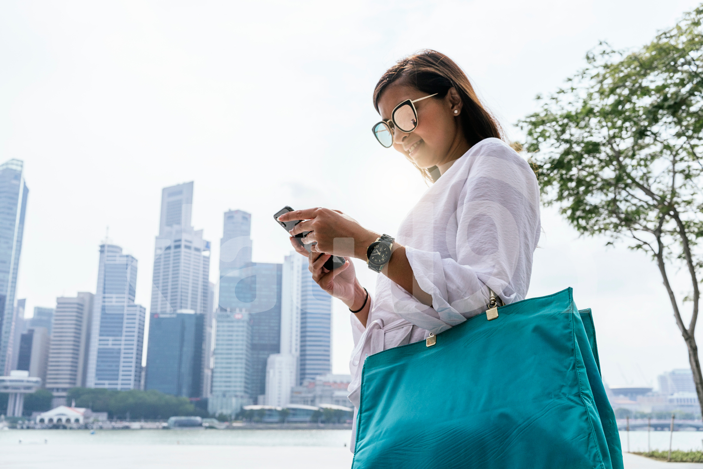 Young Asian woman  using phone, with city as a backdrop