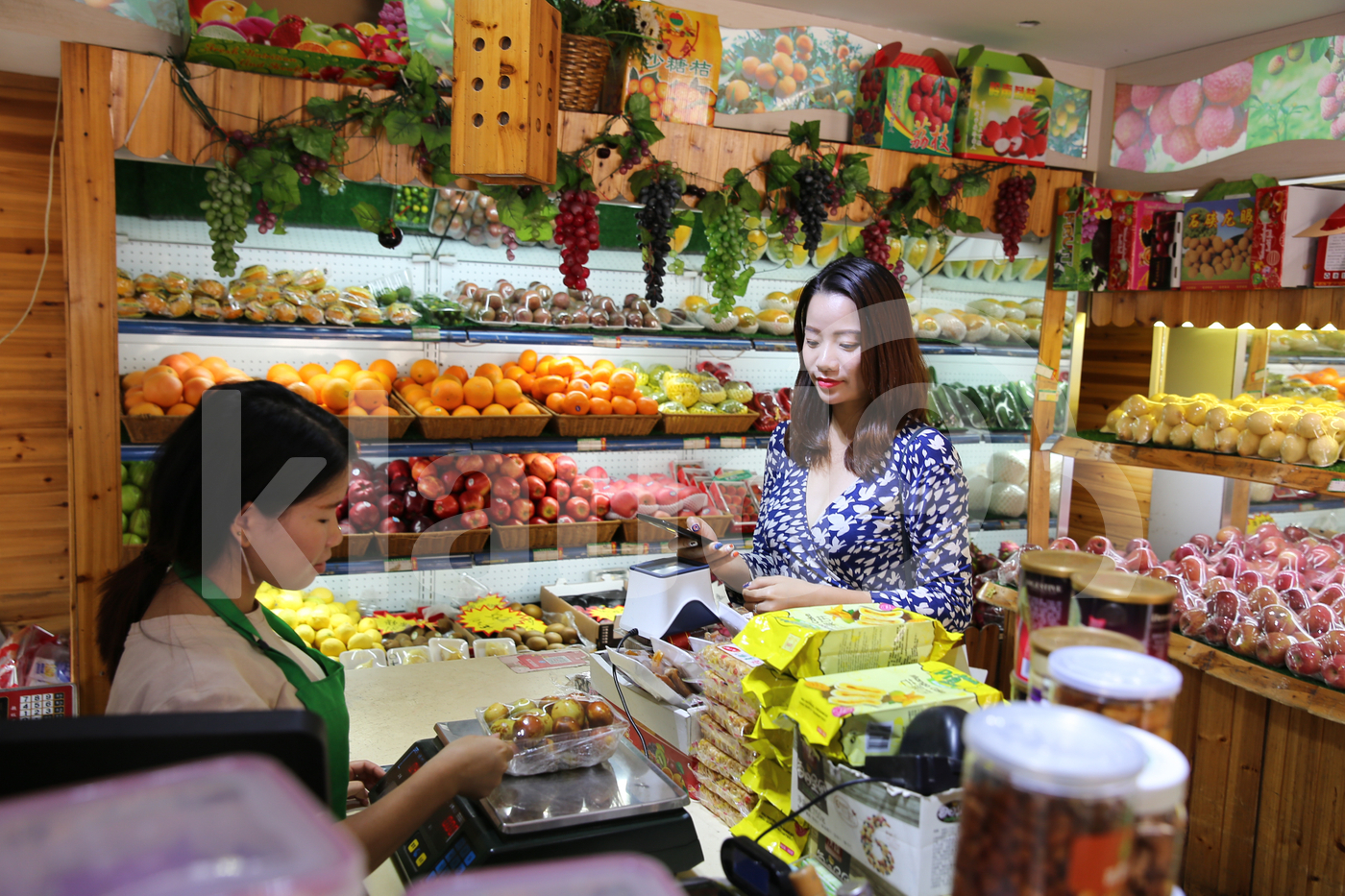 Young Asian woman making payment with mobile in a local shop