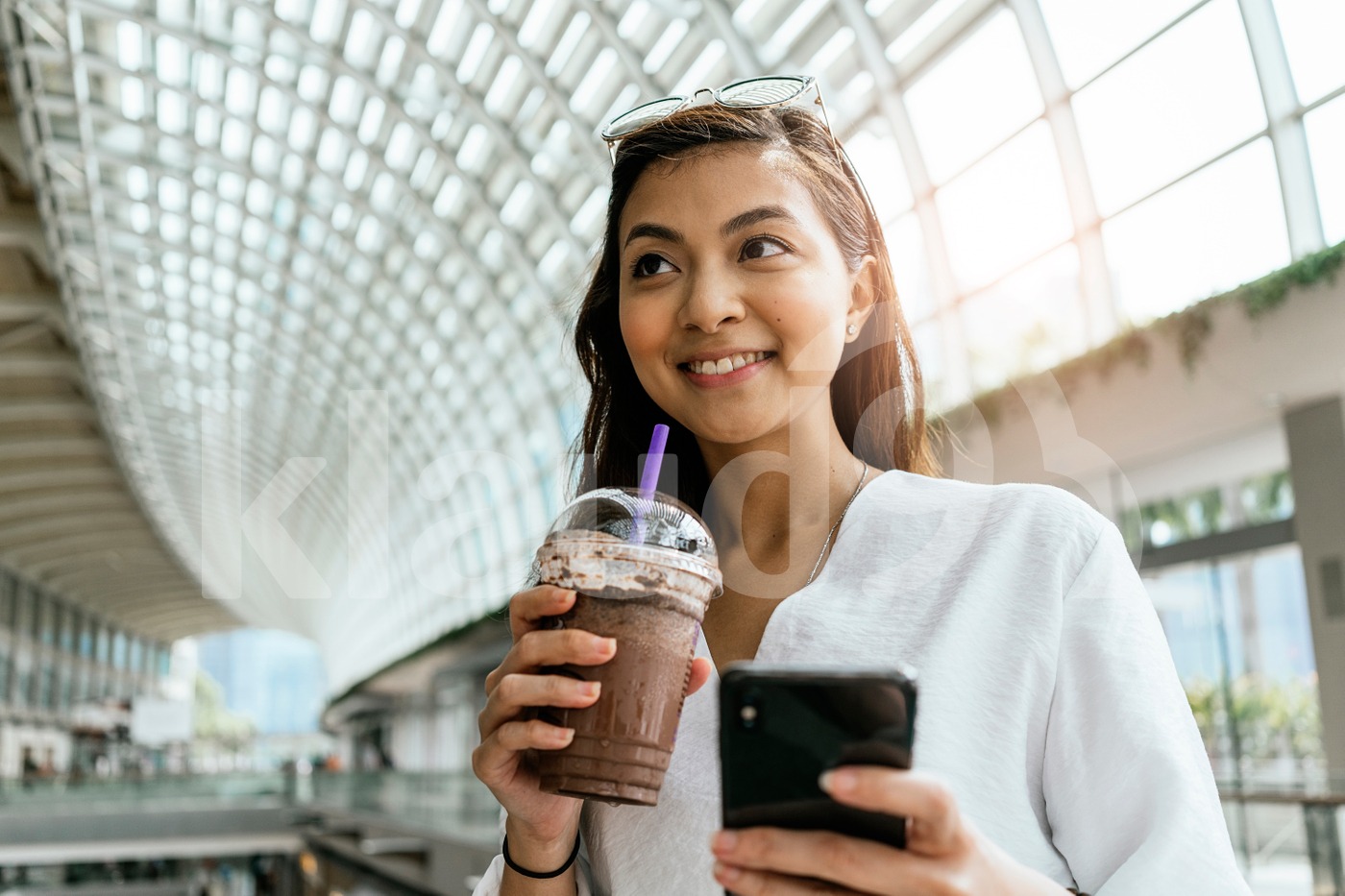 Asian woman using smartphone while drinking a coffee