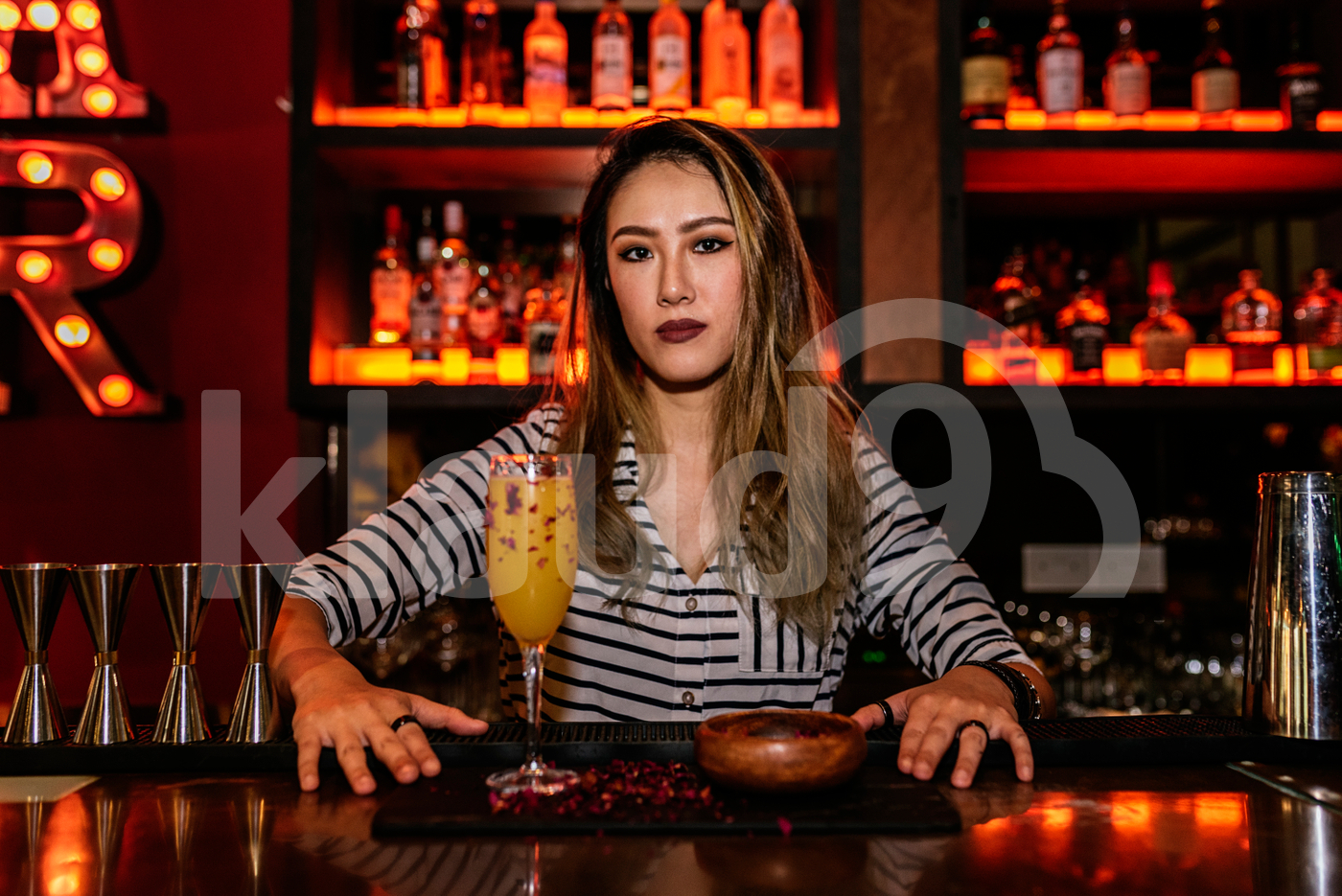 Portrait of female Asian bartender posing with a drink