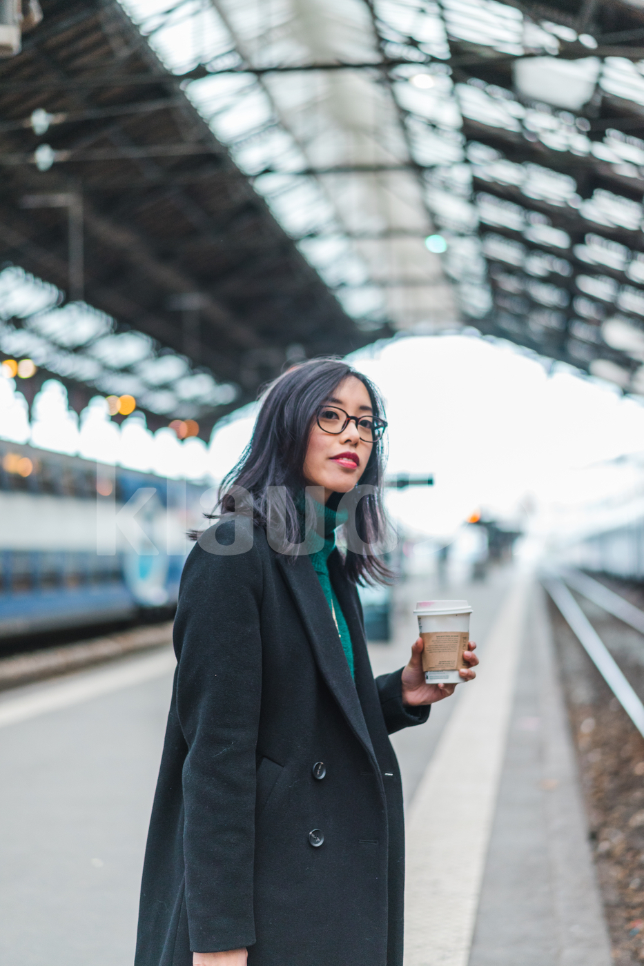 Asian woman waiting for a train holding a drink